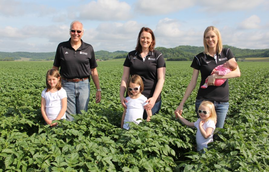 From left to right: Larry Alsum standing in field with daughters, Heidi Randall Alsum and Wendy Dykstra, and grandchildren.